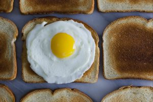 A grid of toast with a sunny side up egg on one.